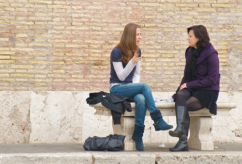 Two young women talking outdoors on a bench